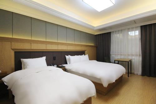 A bed or beds in a room at Duzon Business Hotel