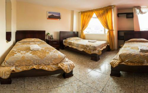 A bed or beds in a room at Hostal La Rosa Otavalo