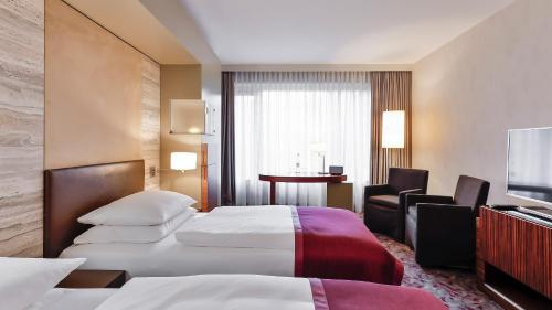 A bed or beds in a room at Dorint Hotel am Heumarkt Köln