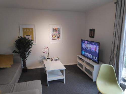 A television and/or entertainment center at Sleek 2BD House with Garden Heart of Guildford