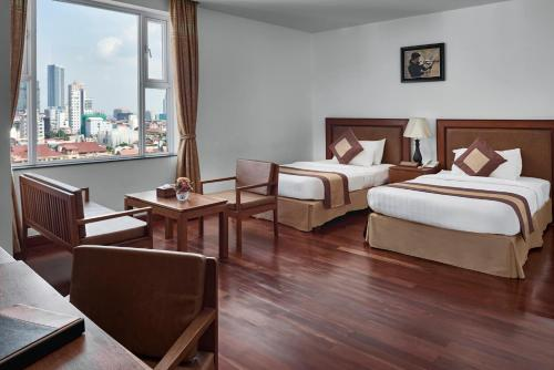 A bed or beds in a room at Phnom Penh Katari Hotel