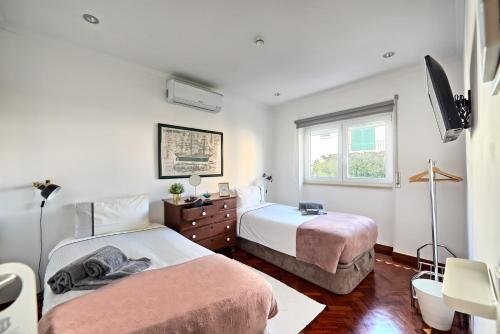 A bed or beds in a room at VillaCerta Rooms Estoril