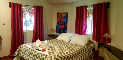 A bed or beds in a room at Paraiso Beach Hotel