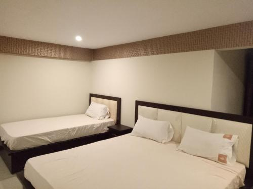 A bed or beds in a room at Pearl Inn