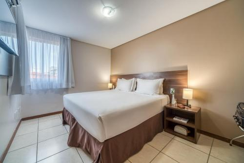 A bed or beds in a room at Intercity João Pessoa