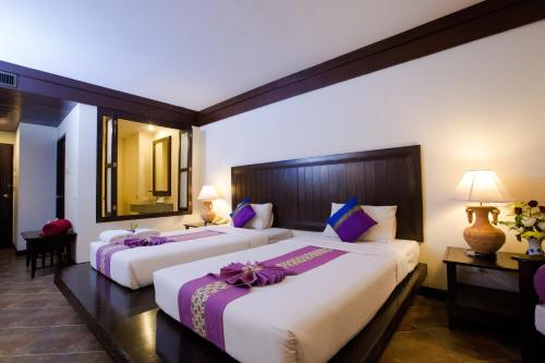 A bed or beds in a room at Kata Poolside Resort SHA Plus