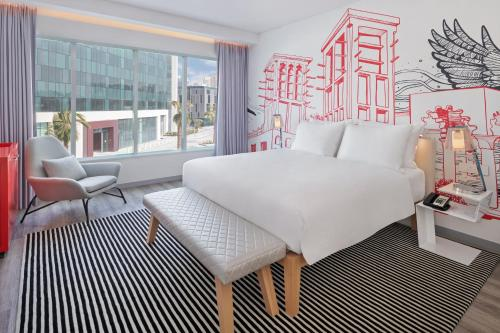A bed or beds in a room at Radisson RED Dubai Silicon Oasis