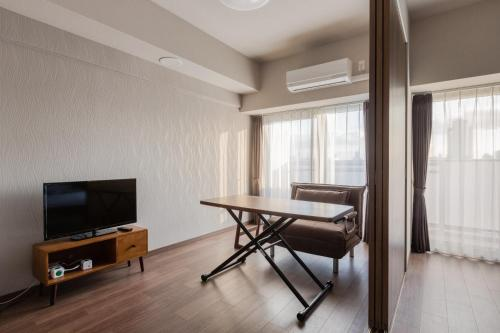 A television and/or entertainment centre at Ostay Shin-Osaka Hotel Apartment