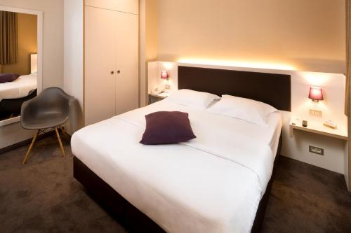 A bed or beds in a room at Hotel Navarra Brugge