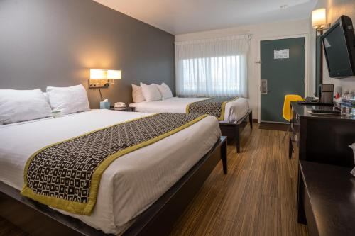 A bed or beds in a room at Park Lane Suites & Inn