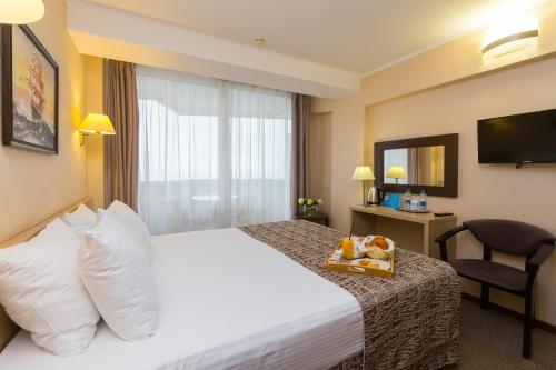 A bed or beds in a room at Sea Galaxy Hotel Congress & Spa