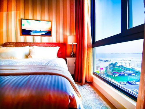 A bed or beds in a room at Beach Front Sea View Apartment Families Only