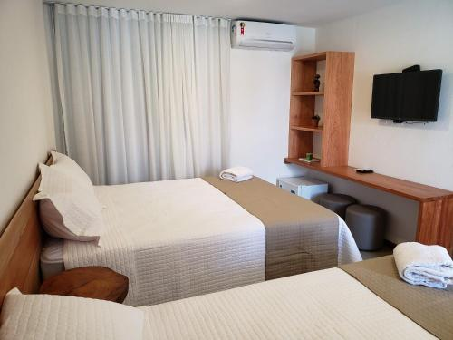 A bed or beds in a room at Pousada Ricoco