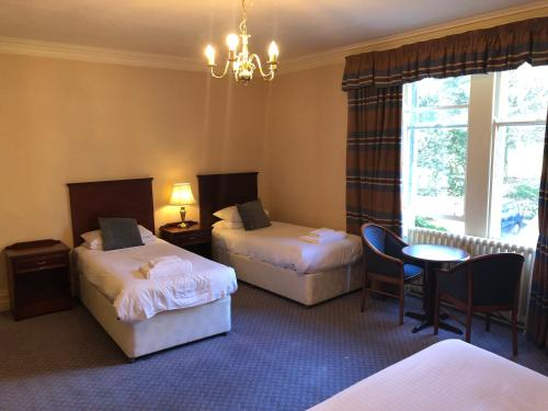 A bed or beds in a room at Cumbria Grand Hotel