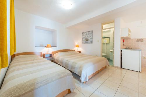 A bed or beds in a room at Villa Carmen Rooms & Apartments