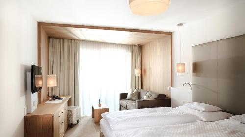 A bed or beds in a room at Hotel Trofana Alpin