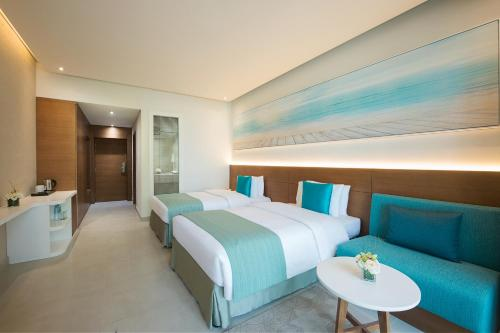 A bed or beds in a room at Wyndham Garden Ajman Corniche