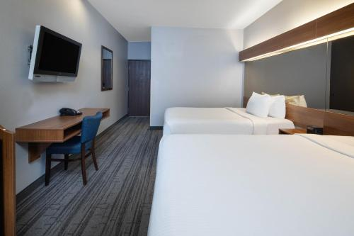 A bed or beds in a room at Baymont by Wyndham Las Vegas South Strip