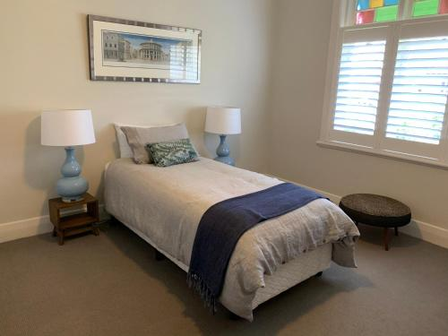 A bed or beds in a room at Frangipani House Cooks Hill