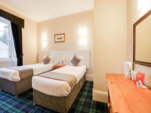 A bed or beds in a room at Lost Guest House Stirling