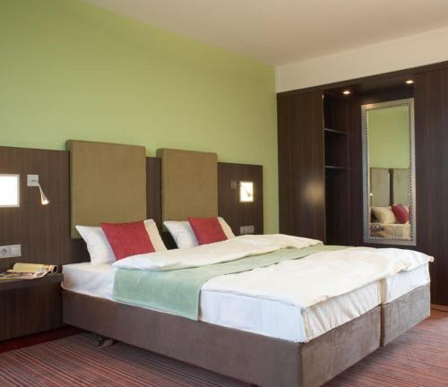 A bed or beds in a room at Qualitel Wilnsdorf