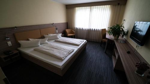 A bed or beds in a room at Hotel Zur Heide