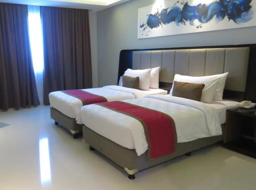 A bed or beds in a room at Prime Plaza Hotel Kualanamu