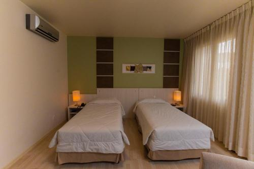 A bed or beds in a room at Locanda Hotel