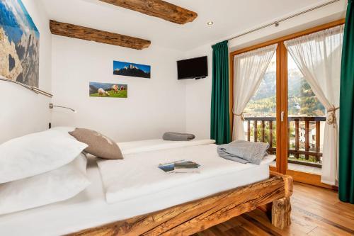 A bed or beds in a room at B&B Sot l'Agner - Ospitalità Diffusa Conca Agordina