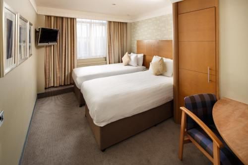 A bed or beds in a room at Mercure Maidstone Great Danes Hotel