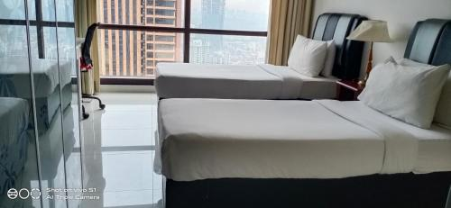 A bed or beds in a room at Bintang Service Suite at Times Square