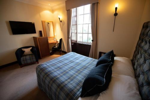 A bed or beds in a room at The Mansefield Hotel