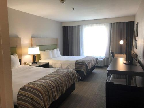 A bed or beds in a room at Country Inn & Suites by Radisson, Ruston, LA