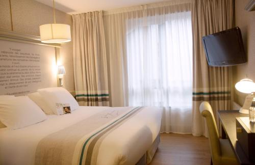 A bed or beds in a room at Best Western Plus Hotel Litteraire Gustave Flaubert