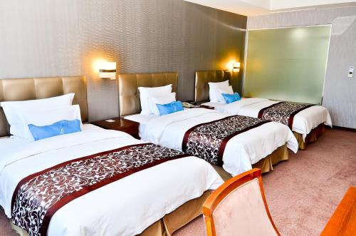 A bed or beds in a room at The Blue Sky Hotel and Tower