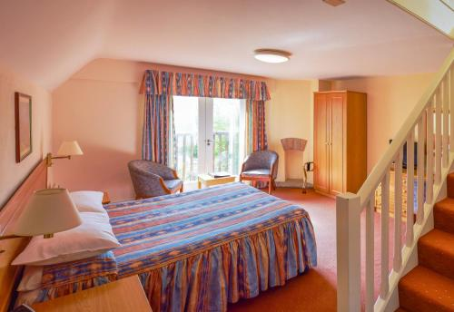 A bed or beds in a room at Louisa Lodge & Purbeck House Hotel