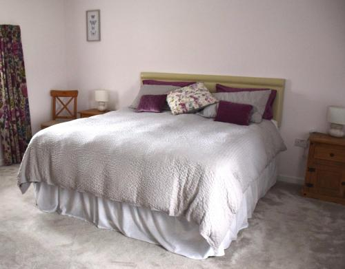 A bed or beds in a room at Tuck Mill Cottage