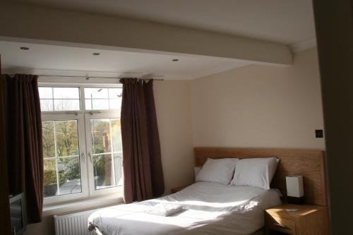 A bed or beds in a room at Clifton Lodge Hotel