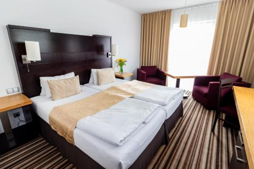 A bed or beds in a room at Parkhotel Plzen