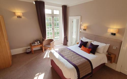 A bed or beds in a room at Chiseldon House Hotel