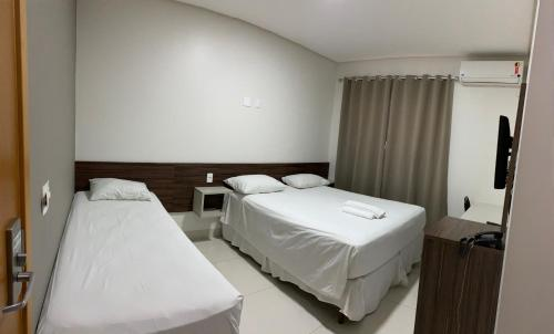 A bed or beds in a room at Hotel Tainá - Aeroporto Cuiabá