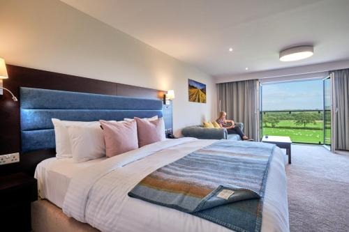 A bed or beds in a room at Llanerch Vineyard Hotel