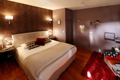 A bed or beds in a room at Hotel Les Pasteliers