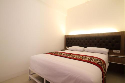 A bed or beds in a room at Apartemen Bassura City by Aparian
