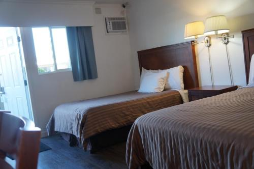 A bed or beds in a room at Westward Inn & Suites