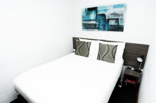 A bed or beds in a room at Bay Hotel Apartments (Previously Apartments at Woolmers)