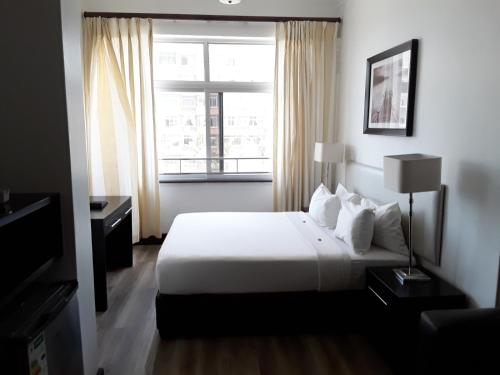 A bed or beds in a room at Parade Hotel