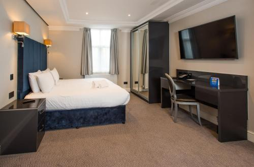 A bed or beds in a room at Best Western Chiswick Palace & Suites London