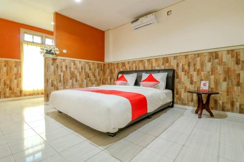 A bed or beds in a room at OYO 2580 Hotel Puri Royan