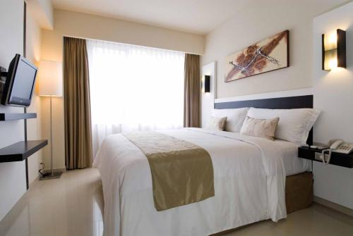 A bed or beds in a room at Aston Denpasar Hotel & Convention